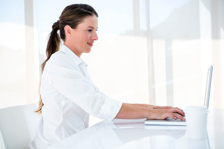 at her desk: smiling business woman, at her desk typing on her laptop
