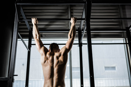 pull out: Shirtless man doing pull up at the crossfit gym