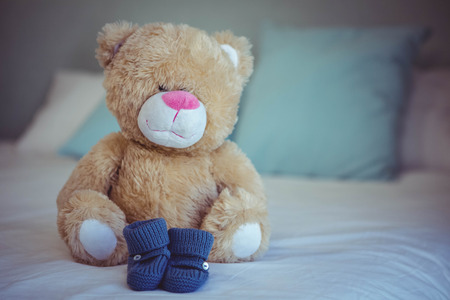 View of teddy bear and baby socks on a bed