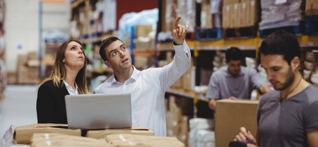 Portret van glimlachende warehouse managers met behulp van laptop