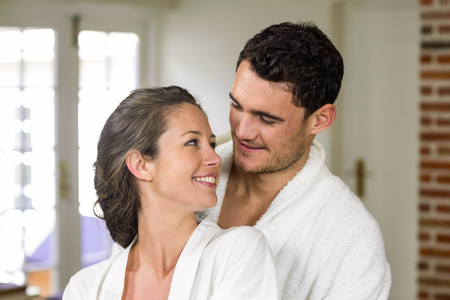 each other: Couple in bathrobe smiling while embracing each other in kitchen