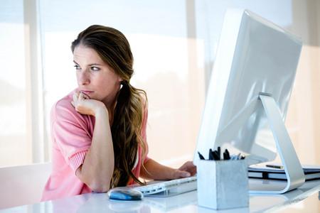 nepozorný obchodní žena, sedící u stolu, při pohledu od svého počítače Reklamní fotografie