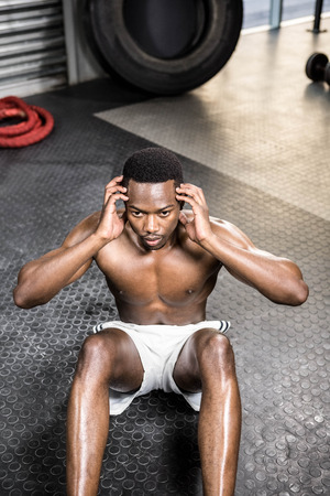 crunches: Muscular man doing abdominal crunches at the crossfit gym Stock Photo
