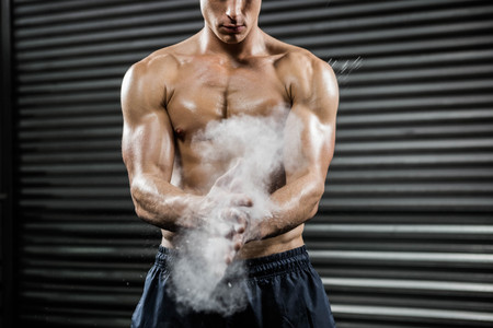 talc: Shirtless man clapping hands with talc at the crossfit gym Stock Photo