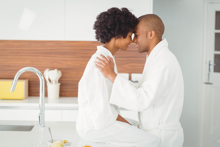 house robe: Happy couple hugging in the kitchen at home