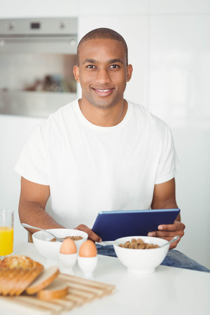 comiendo cereal: Young man using tablet and eating breakfast in kitchen at home