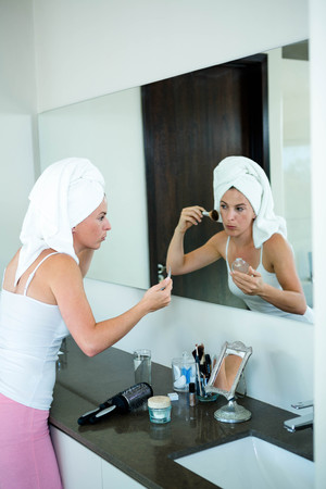face powder: woman wearing a towel on her hair is applying face powder in the mirror