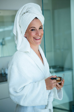 face powder: woman wearing a dressing gown and a towel on her head is holding face powder and a make up brush Stock Photo