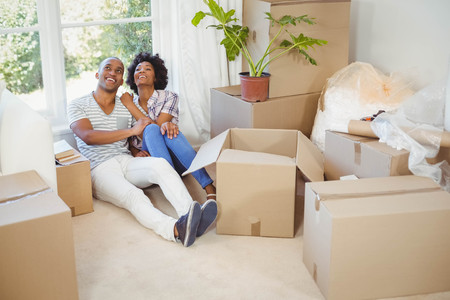 Happy couple sitting on the floor in the living room