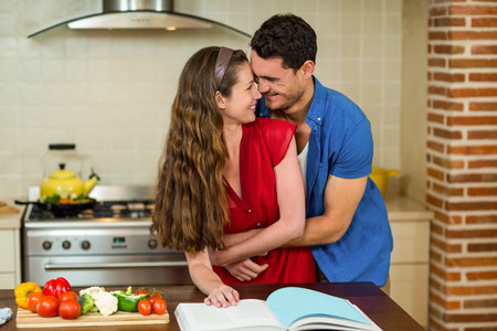 recipe book: Couple embracing in kitchen while checking the recipe book