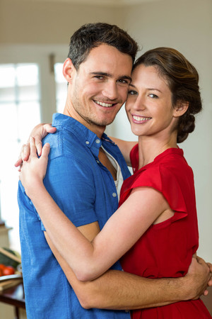 each: Portrait of romantic couple embracing each other in kitchen Stock Photo