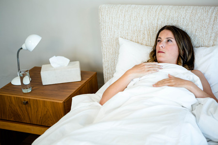 Tissues: sick woman lying in bed surrounded by tissues and water