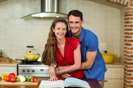 checking ingredients: Portrait of couple embracing in kitchen while checking the recipe book Stock Photo