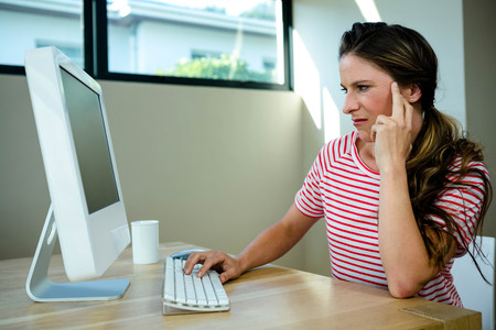 disgruntled: woman looking disgruntled sitting at her desk on hercomputer Stock Photo