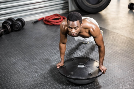 Muscular man doing push up on bosu ball at the crossfit gym Stock Photo
