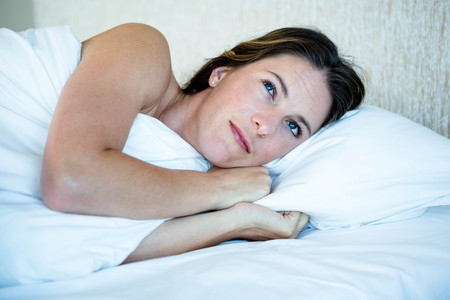 inquiring: woman lying in her bed looking amused