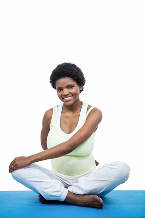white backgroung: Pregnant woman meditating on mat on white backgroung