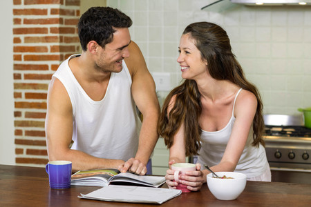 each other: Young couple looking at each other while standing near kitchen worktop
