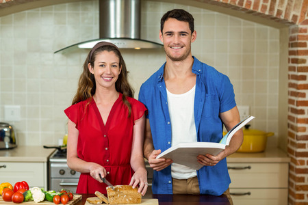 checking ingredients: Portrait of woman cutting loaf of bread while man checking the recipe book in kitchen at home