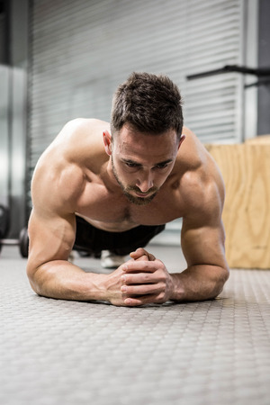 planking: Shirtless man planking at the crossfit gym Stock Photo