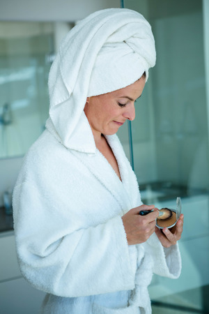 face powder: woman wearing a dressing gown and a towel on her head is holding face powder and a make p brush