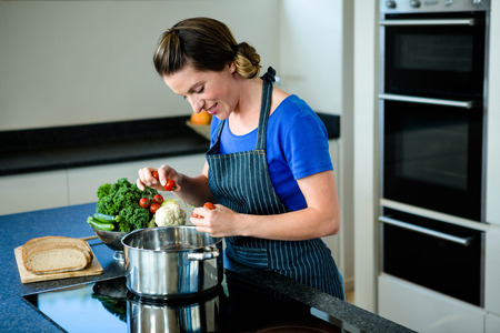 vegtables: smiling woman cooking vegtables in a saucepan on a stove top Stock Photo