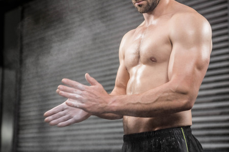manos aplaudiendo: Mediados de secci�n de hombre sin camisa con las manos aplaudiendo talco en el gimnasio CrossFit