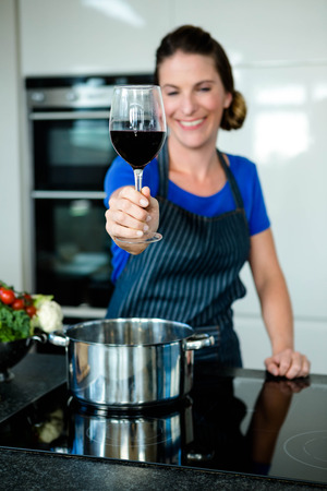 vegtables: smiling woman cooking vegtables in a saucepan on a stove top and drinking red wine