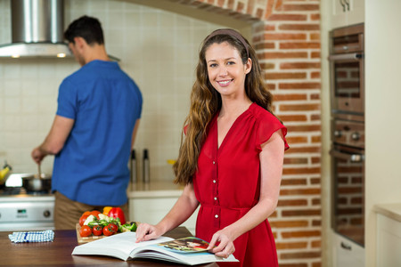 checking ingredients: Woman checking the recipe book in kitchen while man cooking on stove in background Stock Photo