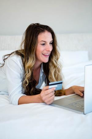 creditcard: woman with brunette hair, lying on her stomach looking at her laptop annd holding her creditcard