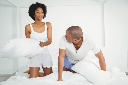 pillow fight: Happy couple having a pillow fight on the bed Stock Photo