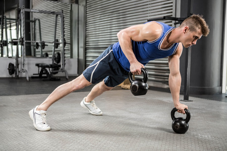 Muscular man doing push up with kettlebells at the crossfit gym