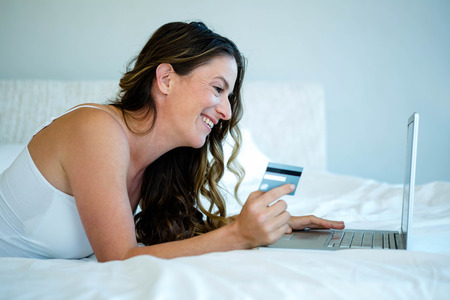chilled out: smiling woman lying down holding her laptop and credit card Stock Photo