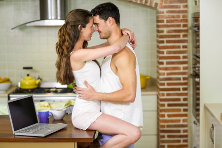 worktop: Romantic young couple cuddling on kitchen worktop