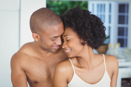 ojos cerrados: Smiling couple hugging with closed eyes at home