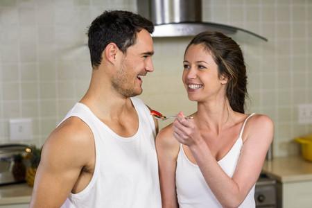 gente adulta: Happy young woman feeding breakfast to her man in kitchen