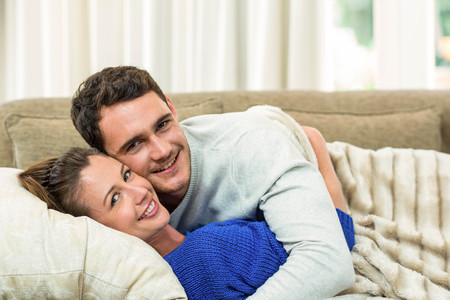 cuddling: Portrait of young couple cuddling on sofa in living room