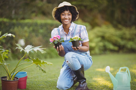 crouching: Smiling woman crouching in the garden holding flowers Stock Photo