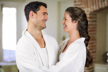 each other: Romantic young couple embracing each other in kitchen