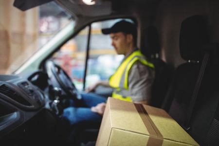 Levering bestuurder driving bestelwagen met pakketten op stoel buiten warehouse
