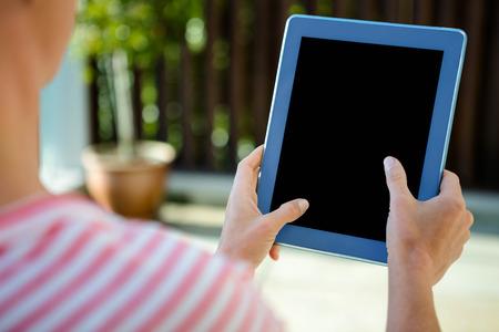 scrolling: female hands, scrolling on a tablet in a garden