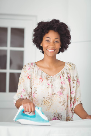 woman ironing: Smiling woman ironing in the kitchen at home Stock Photo