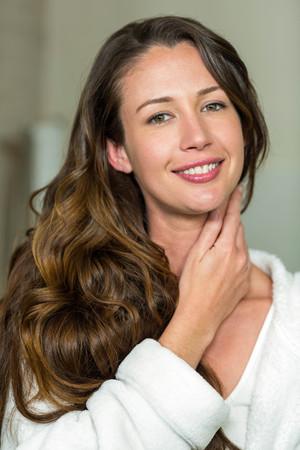 swept: Portrait of beautiful brunette woman smiling in bathroom Stock Photo