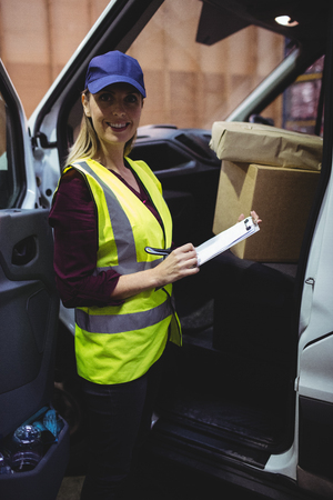 loading bay: Delivery driver checking his list on clipboard in a large warehouse Stock Photo