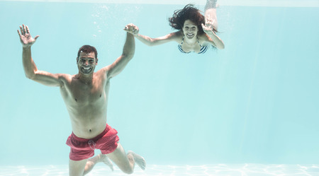 bikini couple: Portrait of underwater couple holding hands and enjoying in swimming pool