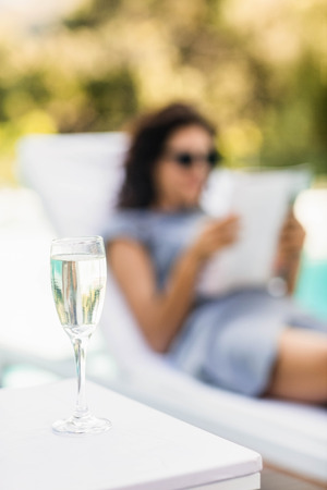 side table: Close-up of champagne flute on side table and woman relaxing on background