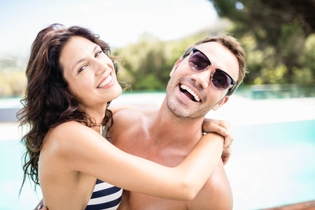 cuddling: Portrait of young couple cuddling each other near pool at sunny day Stock Photo