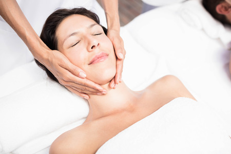 face massage: Woman receiving a face massage from masseur in a spa