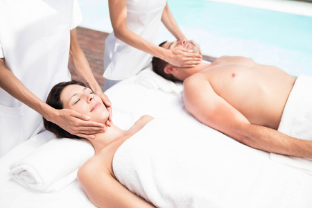 Receiving: Couple receiving a face massage from masseur in a spa