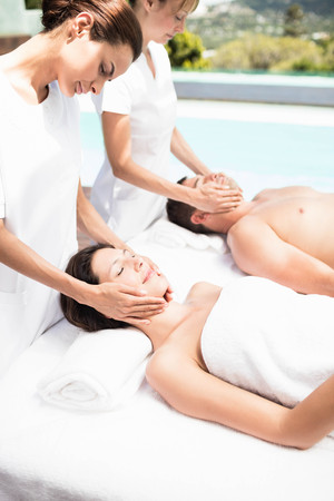 Receiving: Couple receiving a face massage from masseur in spa Stock Photo